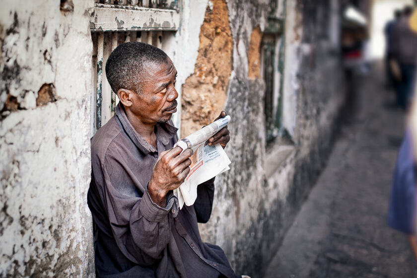 A Zanzibari man looking up from his newspaper in a Stone Town alley.
