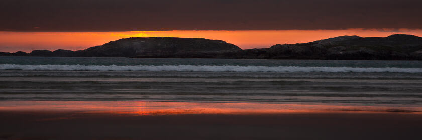An orange red sunset falls over Uig Bay on the Isle of Lewis and Harris
