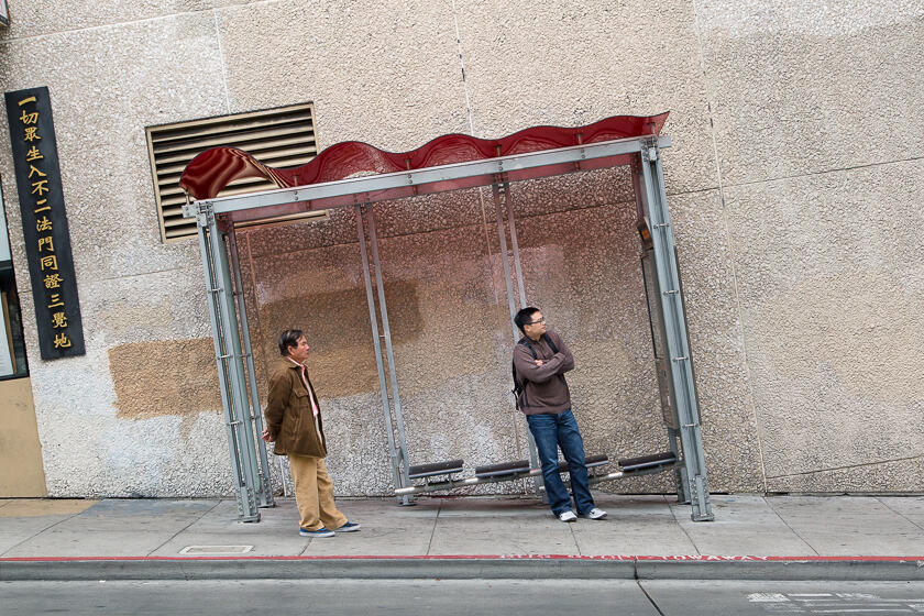 2 men waiting at a bus stop on a very steep road in Chinatown, San Francisco