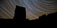 Startrails and shooting star in the Lake District, with a disused mine shaft tower in silhouette.