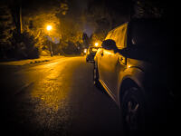 A Mini Cooper lit by a street light at night in Orpington.