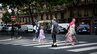 A man roller skating over a zebra crossing in Paris, with a family walking behind going in the opposite direction.