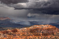 Rain falls from dark clouds above a red-orange landscape of hoodooes and coniferous trees.