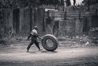 A man rolling a huge tyre along a dust road in Arusha, Tanzania.